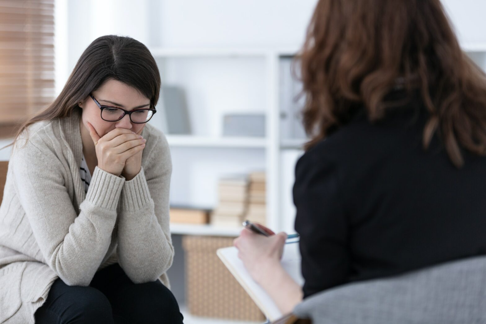 Sad woman crying during psychotherapy at professional clinic